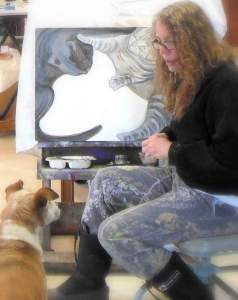 photo of the artist Elizabeth Lisa Petrulis in studio w unfinished Cat Fight and Sadie looks on.