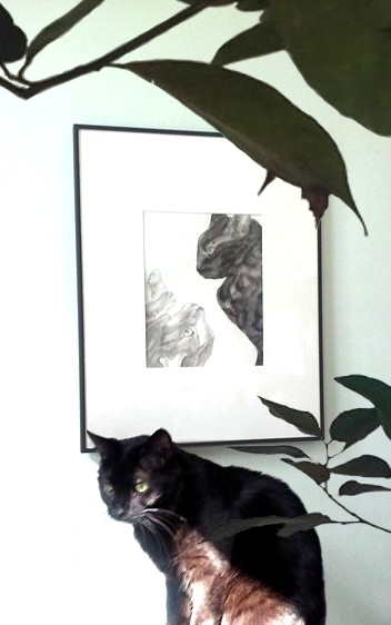 A photograph of the painting Strife on the wall and the rescued cat Coal sitting in front of it under a house plant.