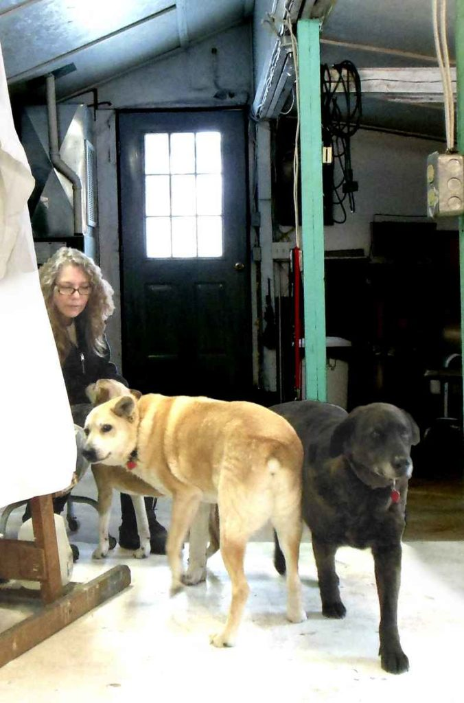 Photo of Elizabeth Lisa Petrulis in front of draped easel and withthe three dogs Sadie, Dino, and Mookie.
