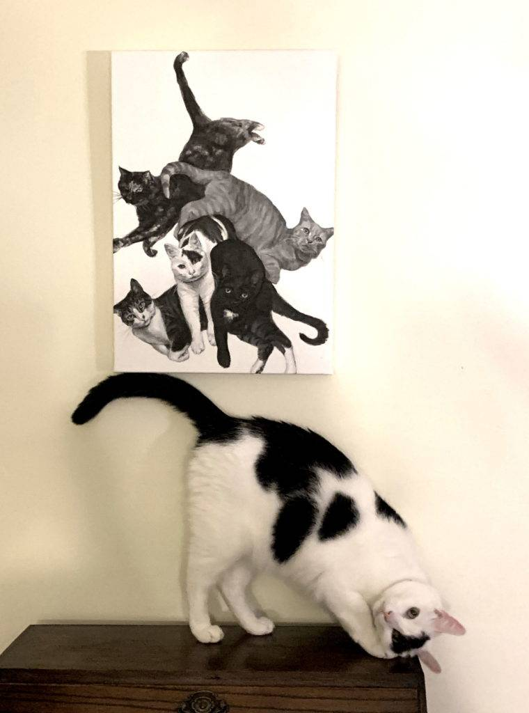 painting of five cats hung above one of the cat models posing on a cabinet
