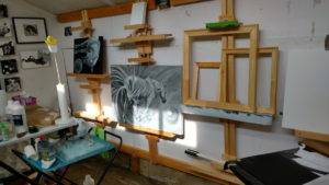 a wall of wooden easels and two black and white paintings of horses with balls, among other canvases, disrupted by rectangles of light cast from a window