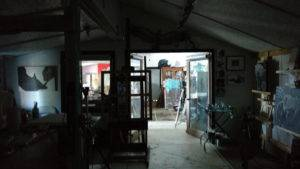 a view from the darkened front of the studio through the window and open doors of the dividing wall into the naturally lit back room